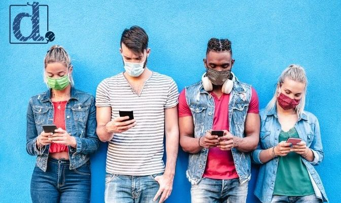 Generation Z members wearing masks and looking at their phones